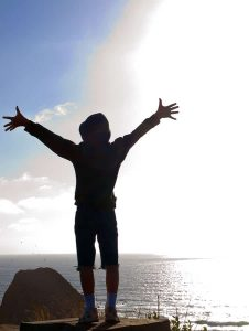 Happy, Young Boy Looking Out Over the Ocean and Bright Sun from a Cliff Edge